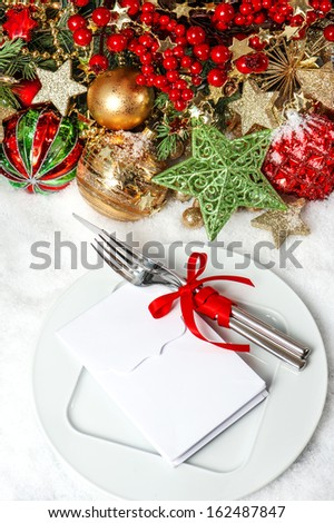 festive table place setting decoration with baubles, golden garlands, candle, christmas tree and red berries. candle light dinner invitation concept with place for your text - stock photo