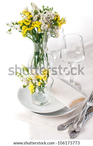 Festive table setting and decoration with fresh flowers in yellow colors - stock photo