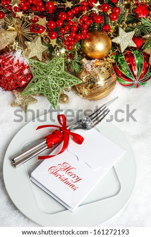 festive table setting decoration with baubles, golden garlands, candle, christmas tree and red berries. dinner invitation concept with sample text Merry Christmas - stock photo