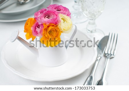 Festive table setting with a bouquet of colorful buttercups flowers in watering can, vintage crockery and cutlery, wedding party, close up - stock photo