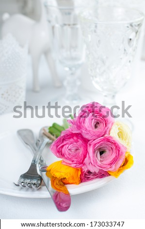 Festive table setting with a bouquet of colorful buttercups flowers, vintage crockery and cutlery, wedding party, close up - stock photo