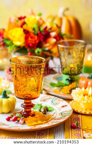 Festive table setting with basket of autumn flowers,candle and pumpkin - stock photo