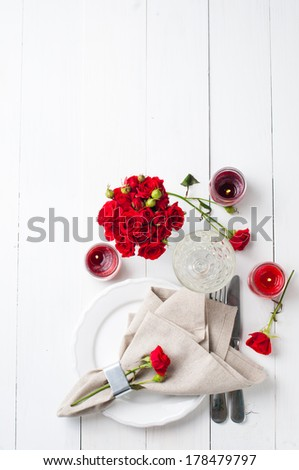 Festive table setting with red roses and candles on white wooden table, decorations on a background, rustic style - stock photo