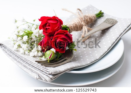 Festive table setting with red roses, napkins and vintage crockery on a white background - stock photo
