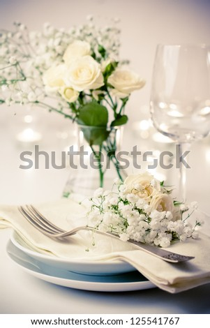 Festive table setting with roses in bright colors and vintage crockery on a beige background - stock photo