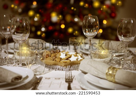 Festive table with christmas tree in the background - stock photo