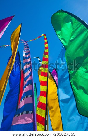 Festive, tall, colorful flags close together are flapping in breezy, windy conditions under a cloudless blue sky. - stock photo