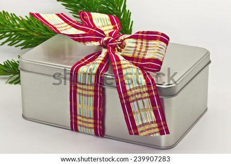 Festive tin gift box with wide ribbon bow. - stock photo