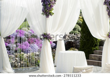 Festive wedding ceremony decoration of lightweight white fabric closeup on purple violet and gtreen natural background, horizontal picture - stock photo
