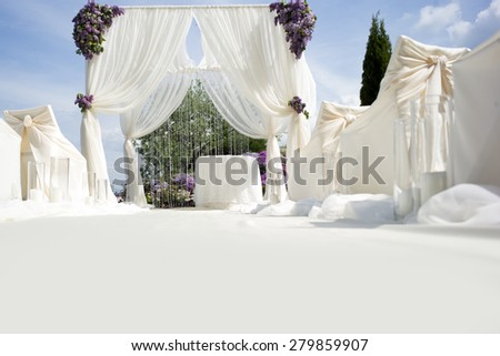 Festive wedding ceremony decoration of lightweight white fabric with light aisle on purple violet and gtreen natural background, horizontal picture - stock photo