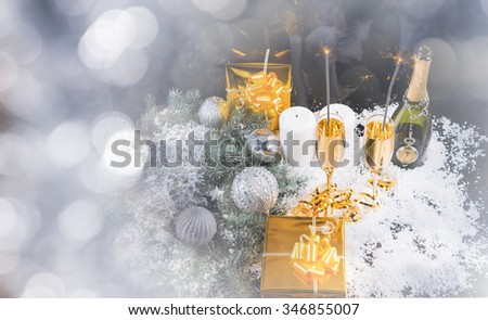 Festive winter Christmas and New Year background with champagne, golden gifts and silver decorations in winter snow surrounded by a sparkling bokeh of party lights - stock photo
