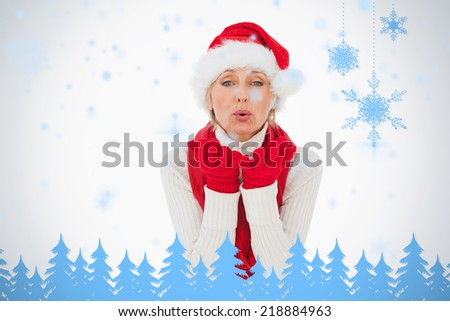 Festive woman blowing a kiss against snowflakes and fir trees in blue - stock photo