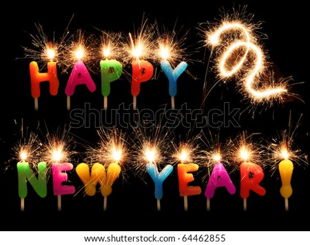 Festive words Happy New Year from colorful candles with sparklers isolated on black - stock photo