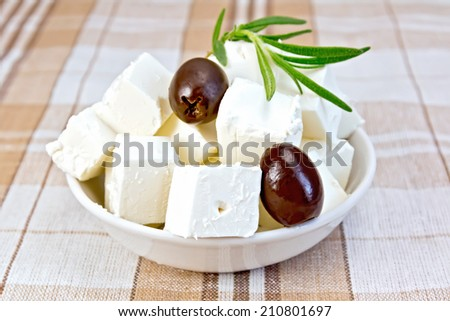 Feta cheese, olives, rosemary in a white bowl on a background of brown tablecloth - stock photo