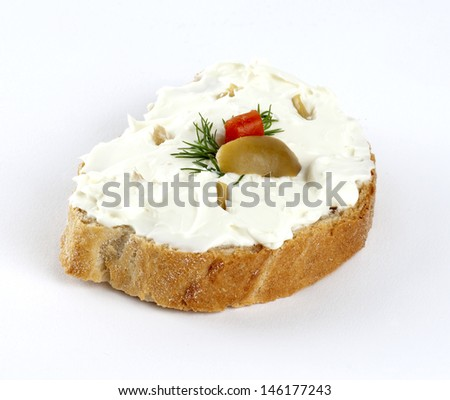 feta cheese spread mixed with green olives and dill on a slice of bread - stock photo