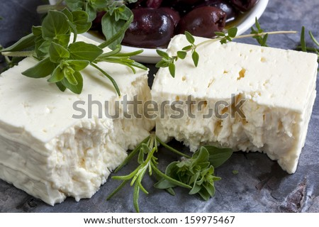 Feta cheese with black olives and fresh herbs. - stock photo