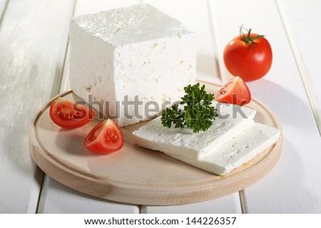feta greek cheese on chopping board white background - stock photo