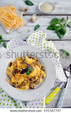 Fettuccine carbonara in a bowl, garnished with quail egg, mushrooms and basil - stock photo