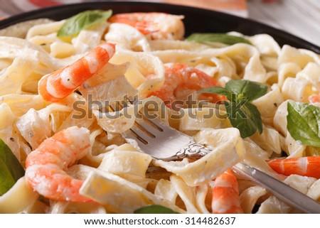 fettuccini pasta in cream sauce with shrimp macro on a plate. Horizontal - stock photo