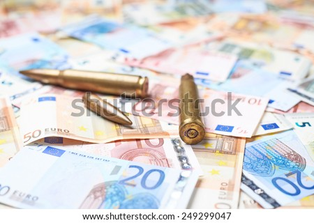 Few ammunition bullet shells over the surface covered with the multiple euro bank note bills - stock photo