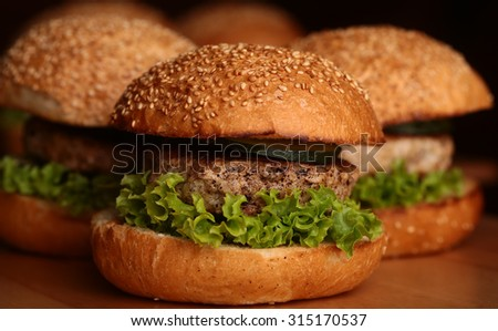 Few big delicious appetizing fresh burgers of green lettuce leaf cheese meat cutlet and white bread bun with sesame seeds on black background closeup, horizontal picture - stock photo