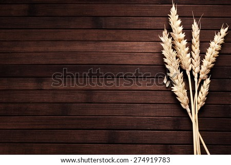 Few ears of wheat on a wooden background. - stock photo