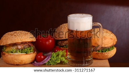 Few fresh tasty burgers of green lettuce meat cutlet tomato and white bun with sesame seeds near and glass of light beer with froth on octoberfest holiday closeup, horizontal picture - stock photo