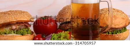 Few fresh tasty burgers of green lettuce meat cutlet tomato and white bun with sesame seeds near and glass of light beer with froth on octoberfest holiday on wooden background, horizontal picture - stock photo