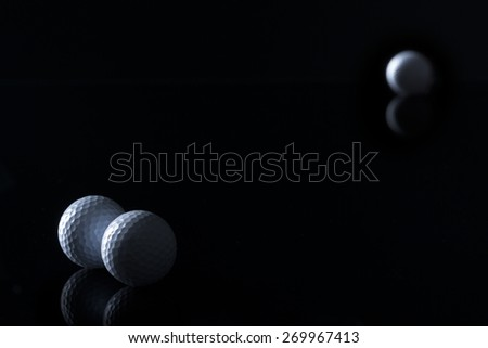 Few golf balls isolated on black background with empty copy space for text. - stock photo