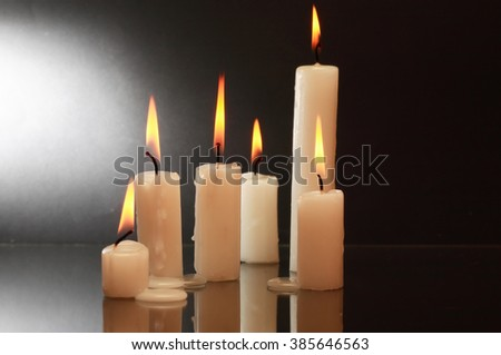 Few lighting candles with reflection on dark background - stock photo