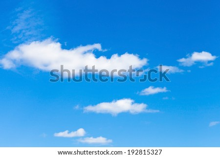 few little fluffy white clouds in blue sky in May - stock photo