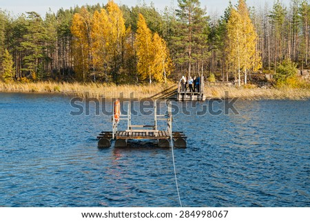 Few people waiting for the ferry to cross the lake in the Repovesi (Finland, South Karelia) - stock photo