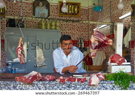 Fez, Morocco - May, 11, 2013: Butcher in an open air Moroccan market - stock photo