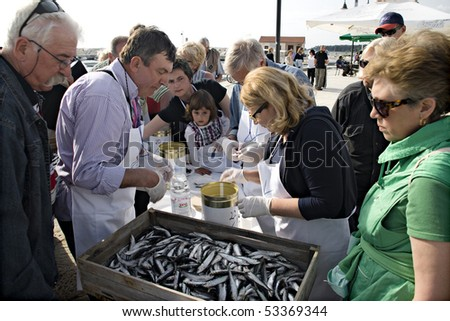 FFAZANA, CROATIA - MAY 1: Tourist and children are learning, how to salt and preserve anchovies on Anchovies Fest on May 1, 2010, in village Fazana, Croatia. - stock photo