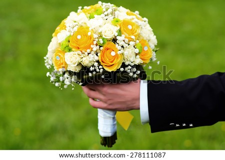 Fiance holding a bright wedding bouquet of white and yellow roses outdoor on green natural background, horizontal picture - stock photo