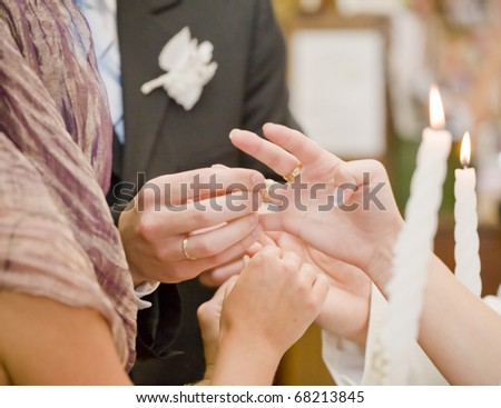 Fiance is putting on wedding ring on bride's finger - stock photo