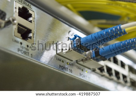 Fibre optic cable connected to an optic ports in a datacenter.(Selective focus) - stock photo