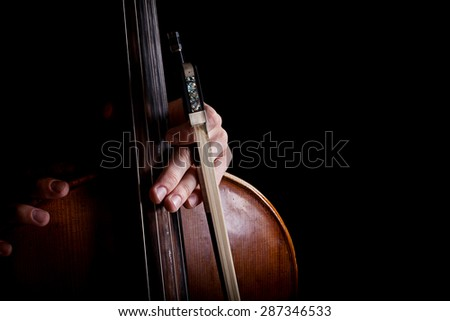 fiddlestick in hand cellist on a black background - stock photo