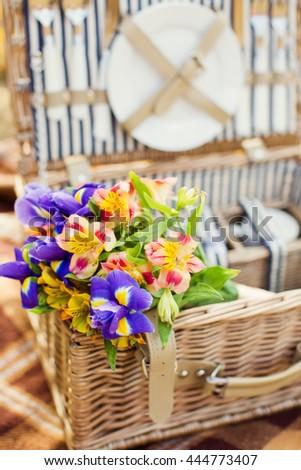 field flowers in picnic basket - stock photo