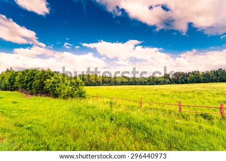 Field in the forest enclosed by a wooden fence on a background of the cloudy sky. Image in the orange-blue toning - stock photo