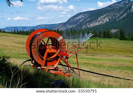 Field irrigation with scenic background - stock photo