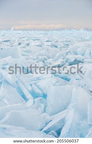 Field of cracked ice hummocks in evening light. Lake Baikal, Siberia. - stock photo