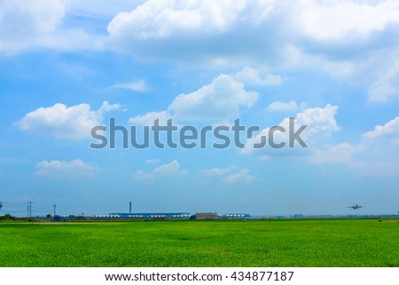 Field of green grass near the airport and sky and clouds background - stock photo