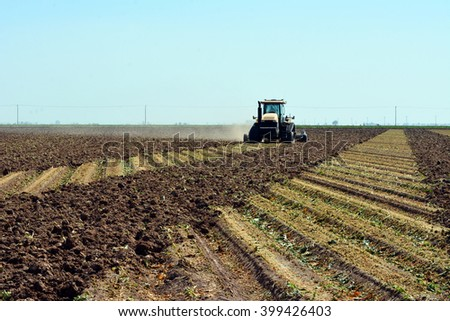 Field of harvested broccoli being plowed under in preparation for planting another crop. - stock photo