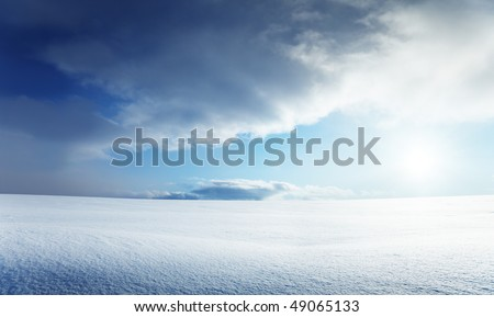 field of snow and cloudy sky - stock photo