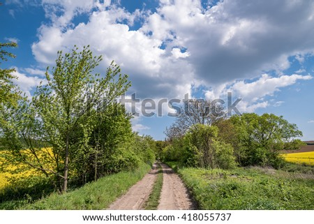 field road with dramatic sky and clouds - stock photo