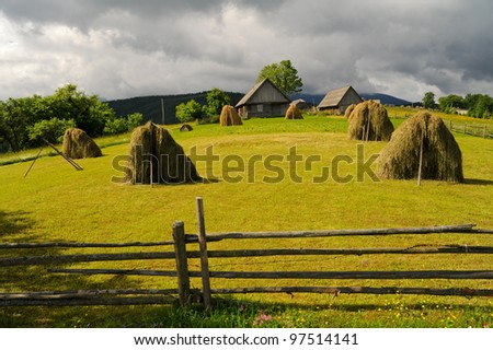 Field with haystack on mountains meadow - stock photo
