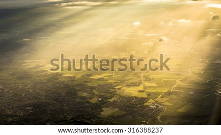 Fields, forest and sunbeam from above - stock photo