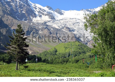 fields, mountains in the snow. Tsey glacier. - stock photo