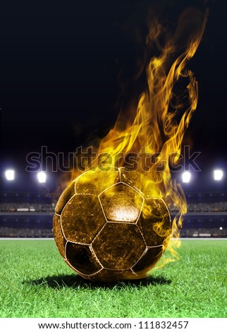 fiery soccer ball on playing field of stadium - stock photo